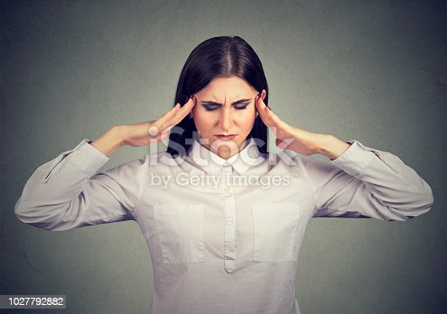 istock Concentrating businesswoman holding fingers on temples 1027792882
