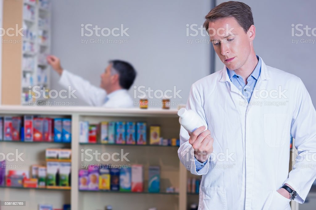 Concentrating pharmacist reading label on medicine jar stock photo