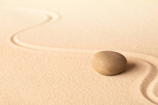 Concentration trough focus on a zen meditation stone Concentration trough focus on a zen meditation stone. Round rock in sand texture background. Concept for yoga or spa welness treatment. spa belgium stock pictures, royalty-free photos & images