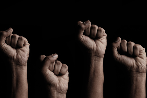 Concept against racism or racial discrimination by showing with hand gestures fist or solidarity.