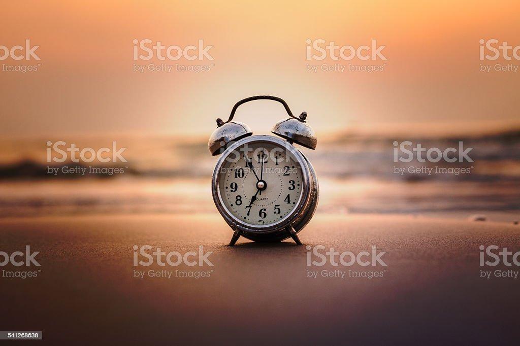 Concept alarm clock on beach still life Retro stock photo