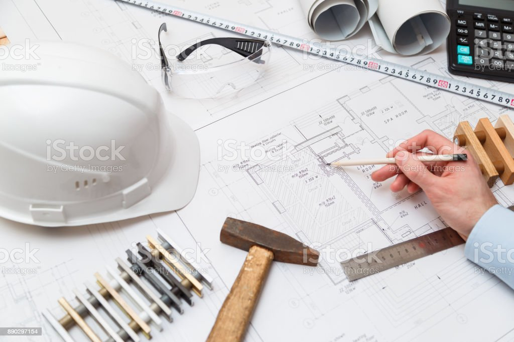Concept architects or engineer holding pencil pointing equipment architects. On the desk with a blueprint in the office. stock photo