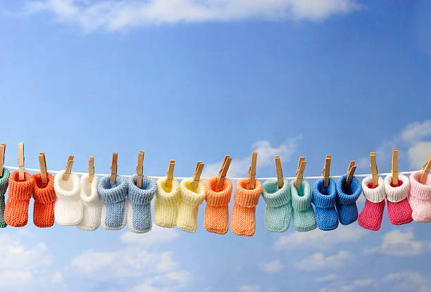 concept: baby booties in a row on clothes line stock photo