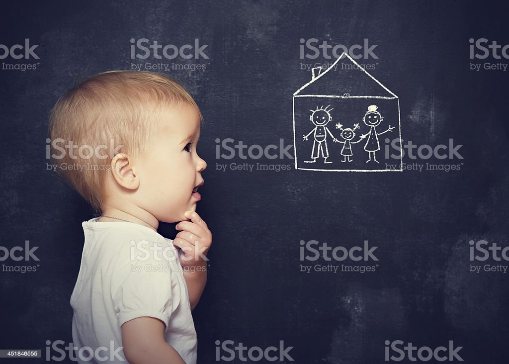 Concept baby looks at board, which is drawn family, home royalty-free stock photo