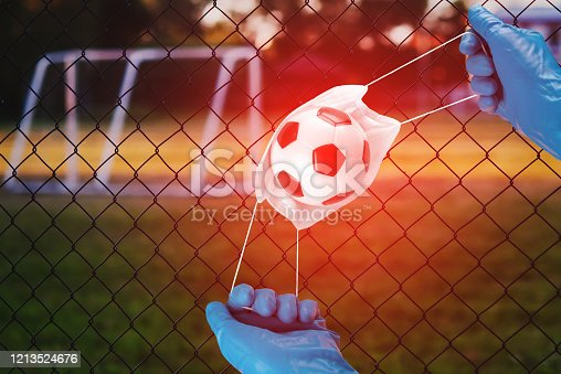 istock Concept banner Cancellation of the football championship due to a coronavirus quarantine.Medical mask with soccers ball in the hands of a medic in blue gloves. Novel coronavirus,2019nCoV, outbreak 1213524676