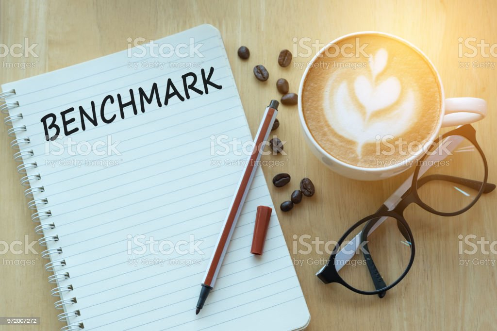 Concept benchmark message on notebook with glasses, pencil and coffee cup on wooden table. stock photo