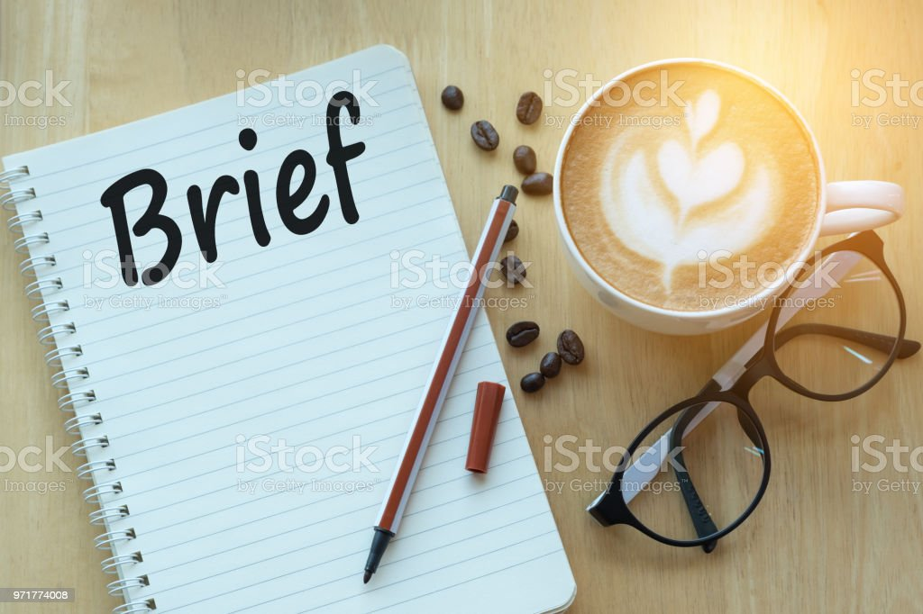 Concept Brief on notebook with glasses, pencil and coffee cup on wooden table stock photo
