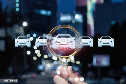 Concept car search. Hand with magnifying glass and icons of the car on the blurred background.