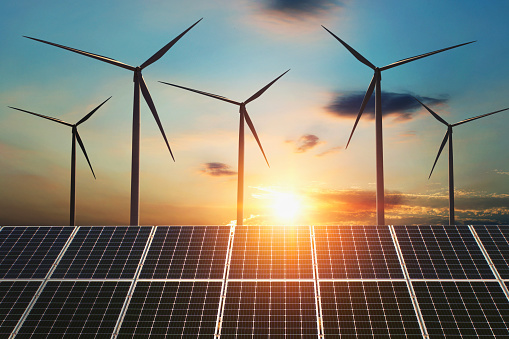 concept clean energy. wind turbine and solar panel in sunrise background