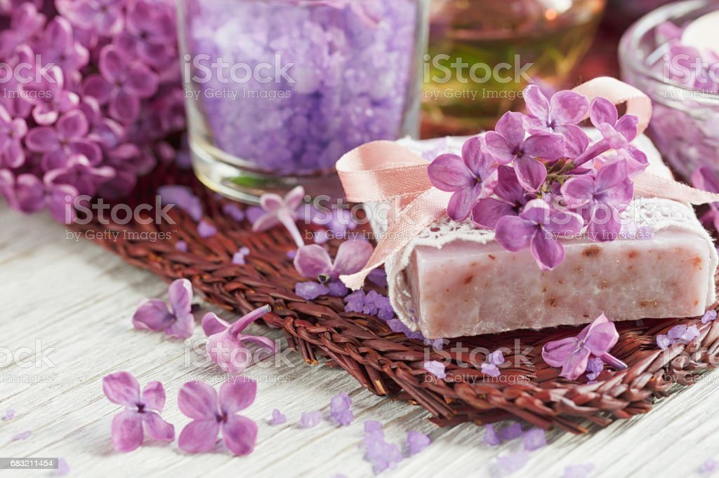 SPA concept: composition of spa treatment with natural sea salt,  aromatic oil and lilac flowers royalty-free stock photo