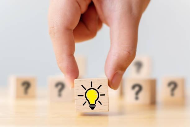 コンセプト創造的なアイデアと革新。手は疑問符記号と電球アイコンで木の立方体のブロックを選んだ - 発見 ストックフォトと画像