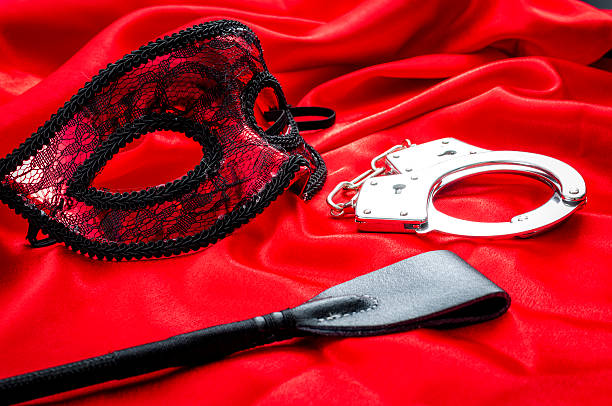 BDSM concept: crop, handcuffs and eyemask on red satin - foto de stock