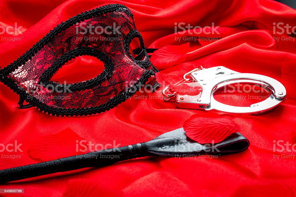 BDSM concept: crop, handcuffs and eyemask on red satin – Foto