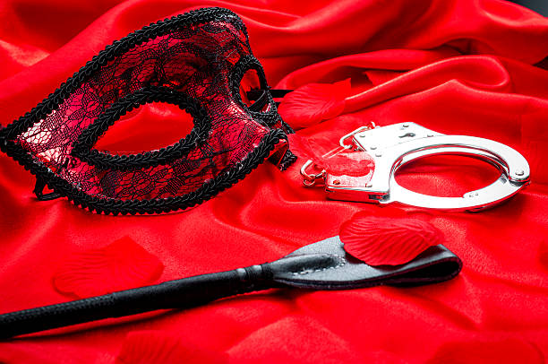 bdsm concept: crop, handcuffs and eyemask on red satin - sm photos et images de collection