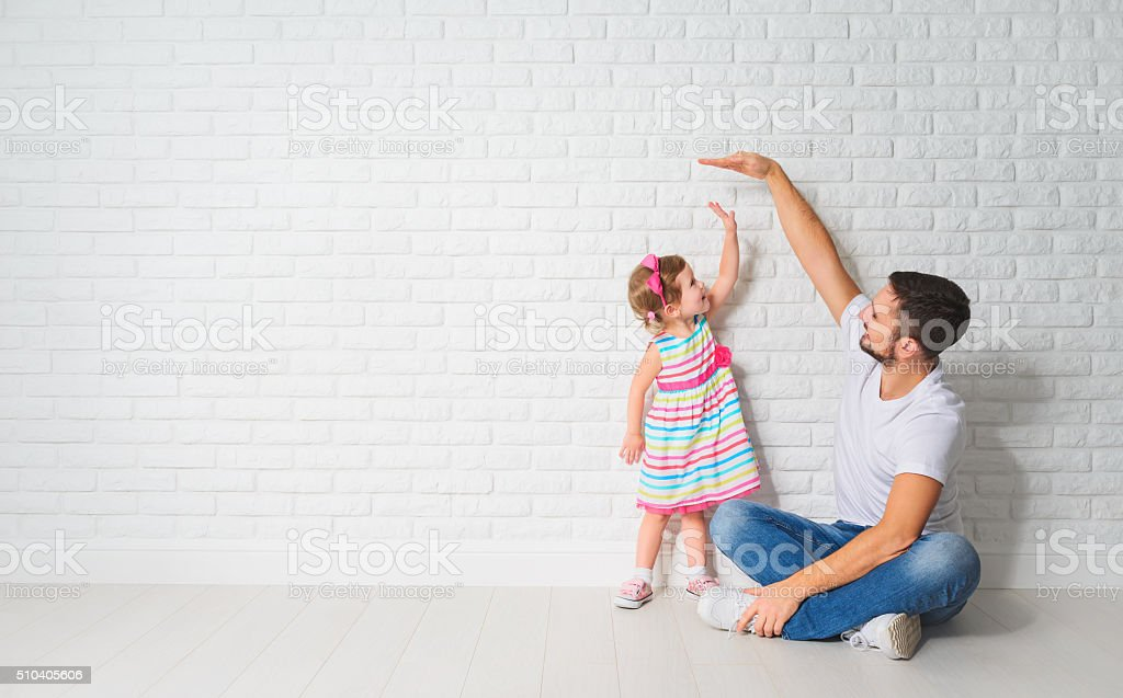 concept. Dad measures growth of her child daughter at wall stock photo