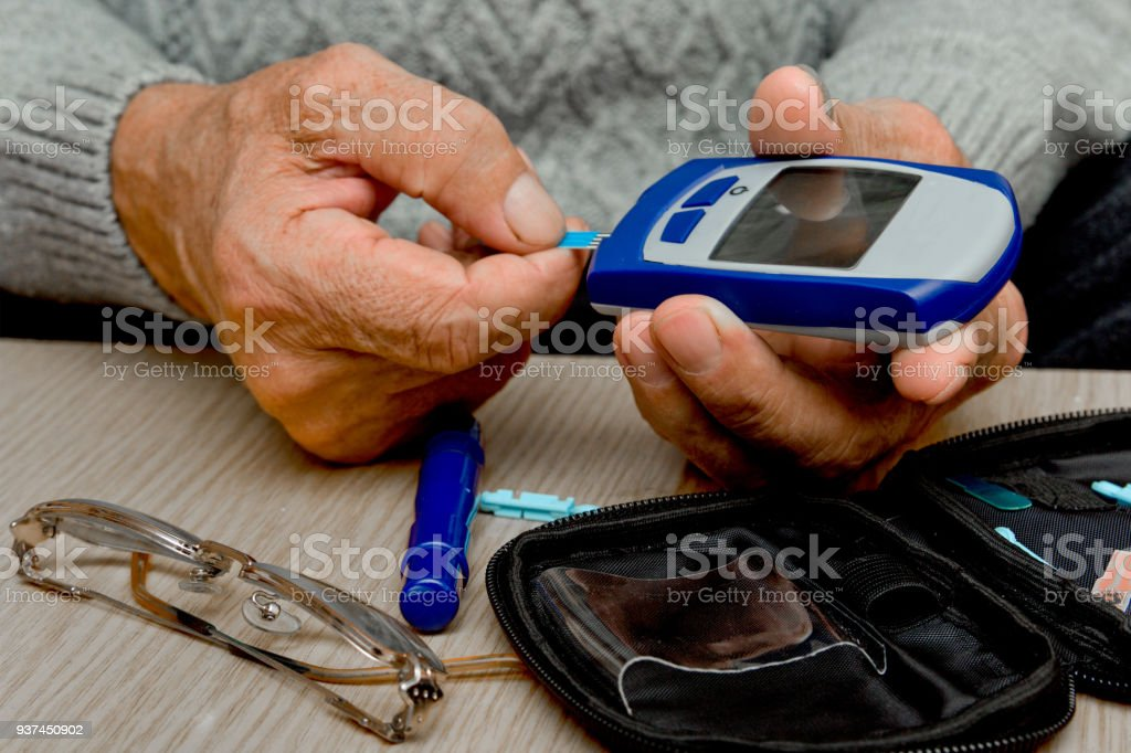 Concept diabetes in the elderly retired. Senior man with glucometer checking blood sugar level at home. Learn to use a glucometer stock photo