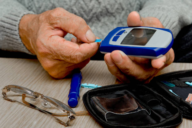 Concept diabetes in the elderly retired. Senior man with glucometer checking blood sugar level at home. Learn to use a glucometer Concept diabetes in the elderly retired. Senior man with glucometer checking blood sugar level at home. Learn to use a glucometer endocrine system stock pictures, royalty-free photos & images