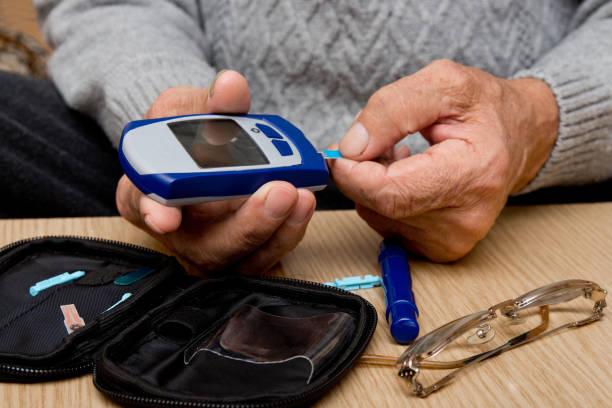 konzept-diabetes bei älteren menschen im ruhestand. ältere mann mit glucometer, die kontrolle des blutzuckerspiegels zu hause. lernen sie, ein glucometer verwenden - hypoglykämie stock-fotos und bilder