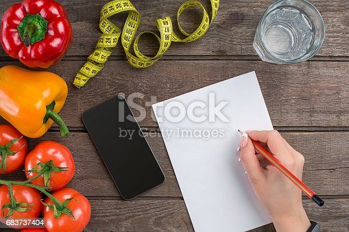 Concept diet, slimming plan with vegetables top view mock up. A female hand in a sports bracelet writes an article about proper nutrition