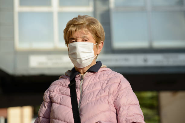 Concept , diseases, viruses, allergies, air pollution. Europe, Italy.  Elderly lady with  protective mask leaving the hospital Concept , diseases, viruses, allergies, air pollution. Europe, Italy.  Elderly lady with  protective mask leaving the hospital. stem cell therapy stock pictures, royalty-free photos & images