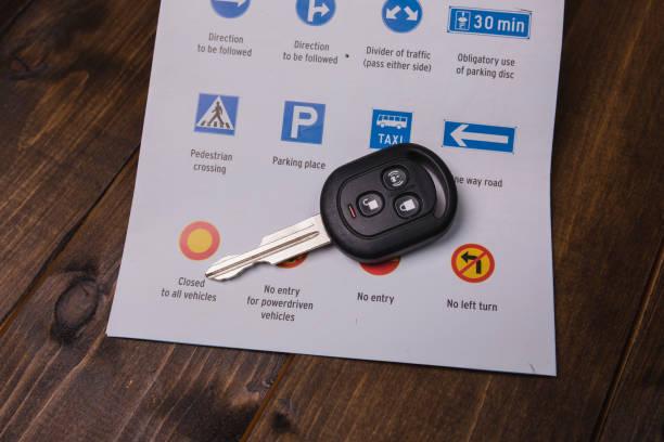 concepto - instrucción de conducción. closeup de señales de tráfico y las llaves del coche - aprender a conducir fotografías e imágenes de stock