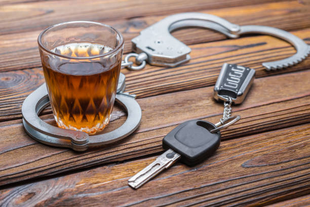 Concept drunkenness driving. Handcuffs, a glass of alcohol, car keys. stock photo
