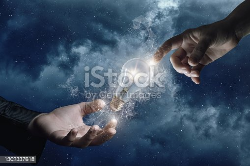 Concept emergence of conceptual idea. Hands click on a burning light bulb in outer space.