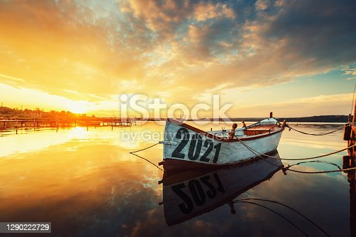 2021 concept Fishing Boat on Varna lake with a reflection in the water at sunset.