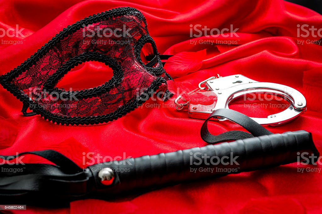 BDSM concept: flogger (whip), handcuffs and eyemask on red satin stock photo