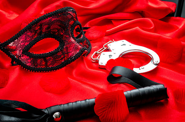 bdsm concept: flogger/whip, handcuffs and eyemask on red satin - sm photos et images de collection