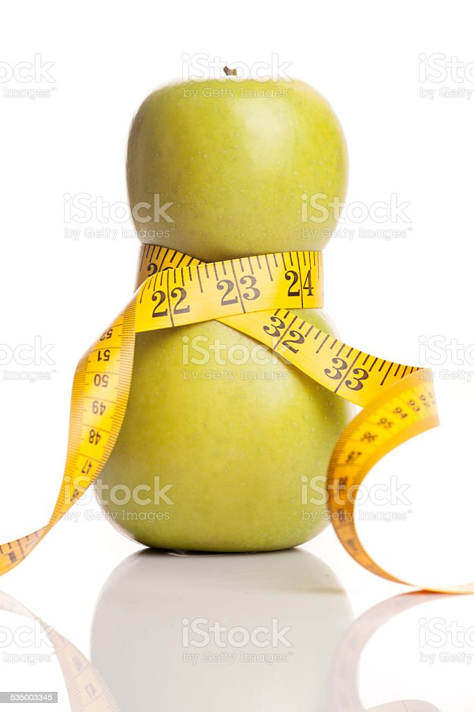 Concept for a diet. Apple wrapped in measuring tape stock photo