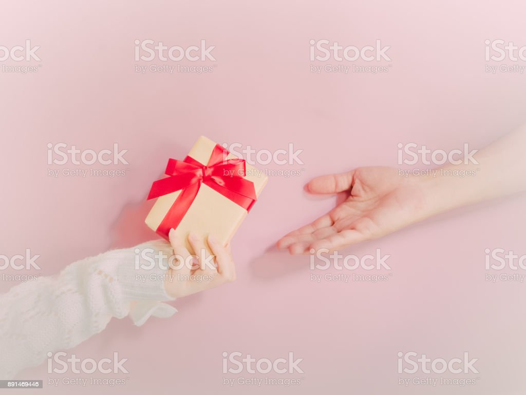concept for christmas and new year event with beauty hand woman with winter cloth holding gift box and give or donate it to pauper person with isolated pink background stock photo