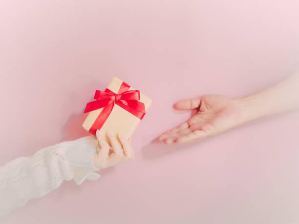konzept für weihnachten und neujahr event mit schönheit hand frau mit winter-tuch mit geschenk-box und geben oder spenden sie für bettler person mit isolierten rosa hintergrund - weihnachtsspende stock-fotos und bilder