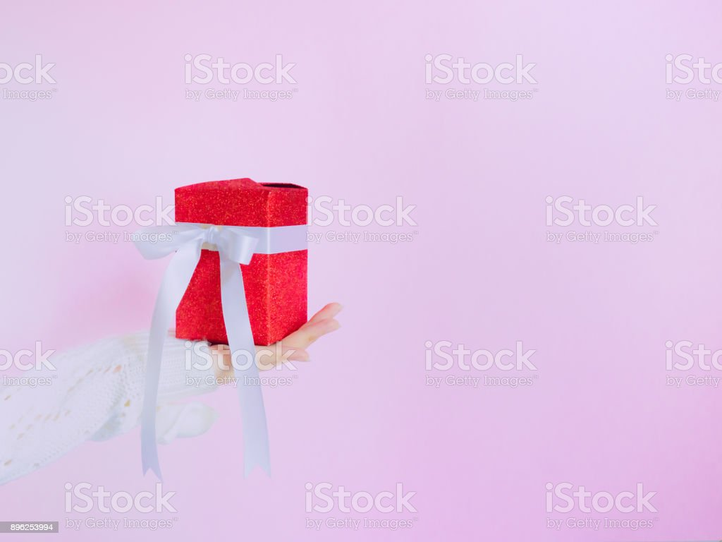 concept for christmas and new year event with beauty hand woman with winter cloth holding gift box and give it to pauper person with isolated pink background stock photo