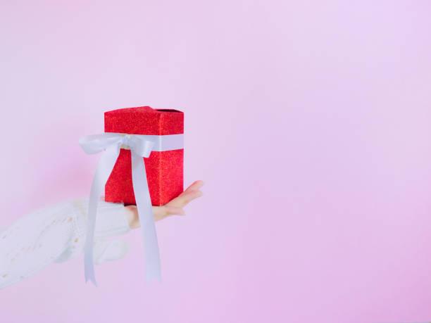 konzept für weihnachten und neujahr event mit schönheit hand frau mit winter tuch hält geschenkbox und gebt es dem bettler person mit isolierten rosa hintergrund - weihnachtsspende stock-fotos und bilder