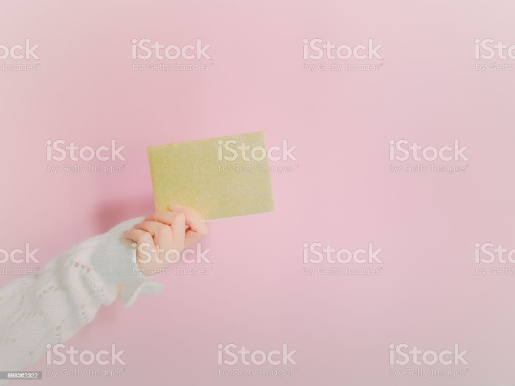 concept for christmas and new year event with beauty hand woman with winter cloth holding greeting card and give it to her respect person with isolated pink background stock photo