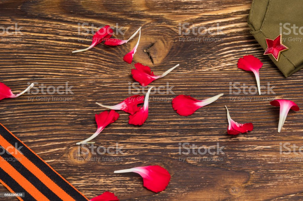 Concept from the petals of a red carnation, on an old wooden table stock photo