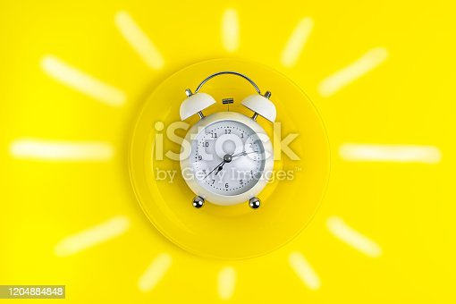1139289535 istock photo concept good morning alarm clock on a yellow plate with painted sunlight. 1204884848