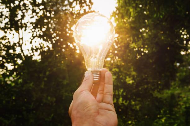 konzept-hand halten glühbirne solare energie in der natur - solarleuchten stock-fotos und bilder