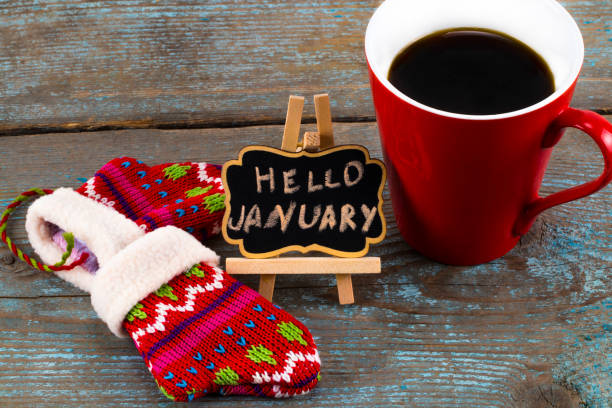 Concept HELLO january message on blackboard with a Cup of coffee and mittens stock photo