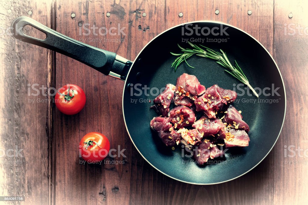 Concept: home cooking.Raw goulash beef in a frying pan with rosemary and spices. royalty-free stock photo