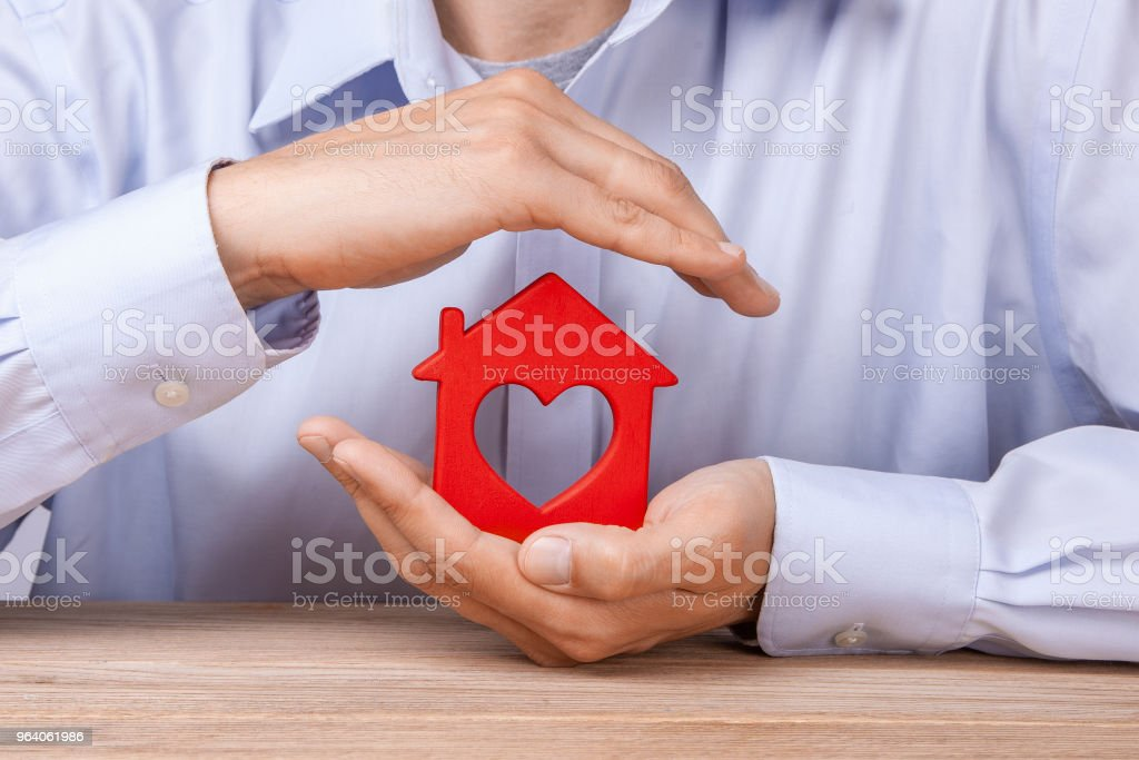 Concept home insurance, protection from burglary or destruction. Man with his hands covers the houses of red color with the heart - Royalty-free Adult Stock Photo
