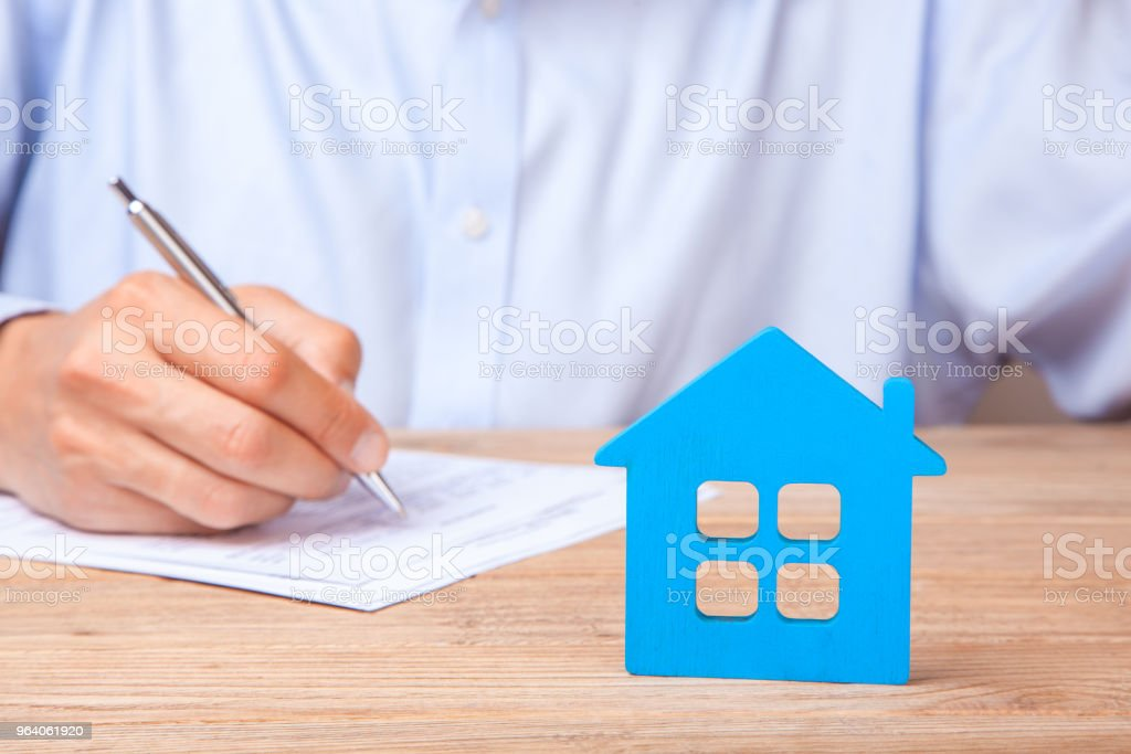 Concept home insurance, rent or purchase. Blue house and Man signs contract - Royalty-free Adult Stock Photo