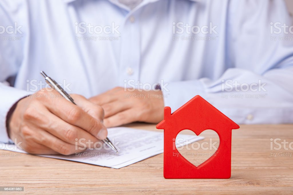 Concept home insurance, rent or purchase. Red house with heart and  man signs contract - Royalty-free Adult Stock Photo