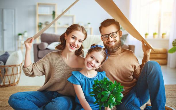 Konzept Wohnen junge Familie. Mutter Vater und Kind in neuem Haus mit Dach zu Hause – Foto