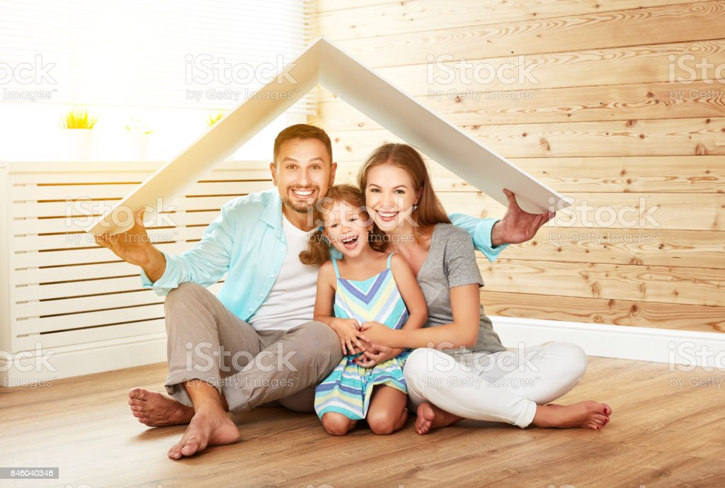 concept housing   young family. Mother father and child in new house with  roof stock photo