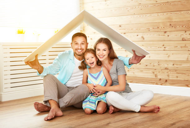 concept housing   young family. mother father and child in new house with  roof - insurance stock photos and pictures