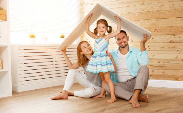 concept housing   young family. mother father and child in new house with  roof - safe stock photos and pictures