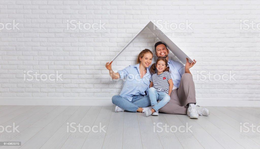 begreppet bostäder ung familj. Mor far och barn i nya hus med tak på tom tegelvägg bildbanksfoto