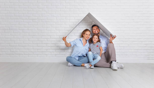 concept housing   young family. Mother father and child in new house with  roof at empty brick wall stock photo